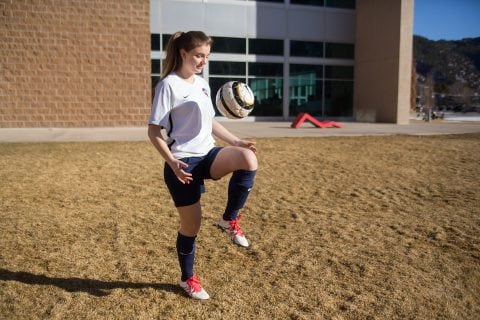 A soccer player bouncing a ball on her knee